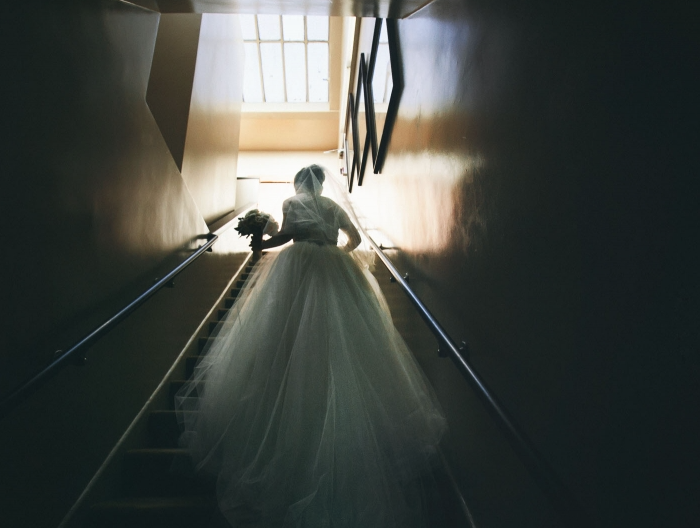 Woman in wedding dress going up stairs